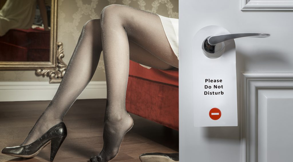 "Image of woman sitting on a chair wearing panty hose behind a door with a ""Please do not disturb"" sign on it"