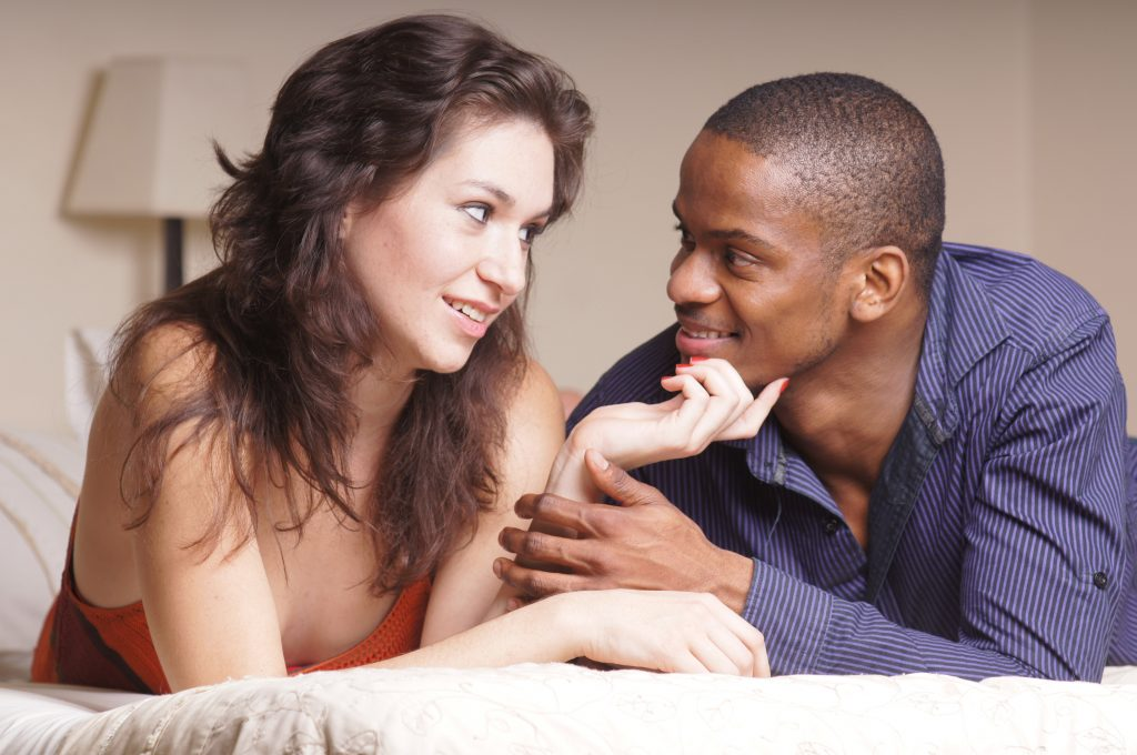 Man and woman on bed together smiling at each other.