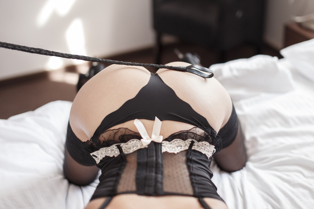 Woman bent over on bed being smacked with a riding crop.