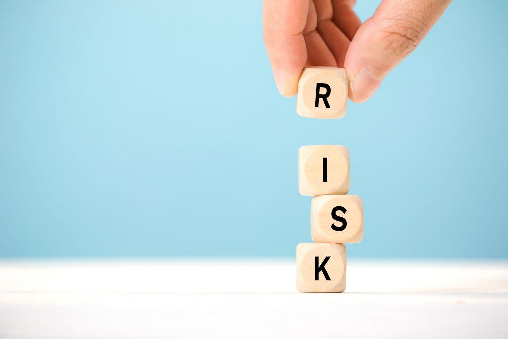 "Wooden blocks stacked on top of each other spelling the word ""Risk"""