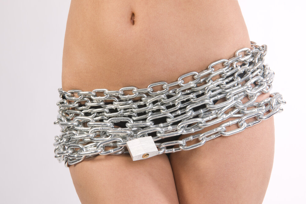Woman's midsection with chains wrapped around her pelvis padlocked together